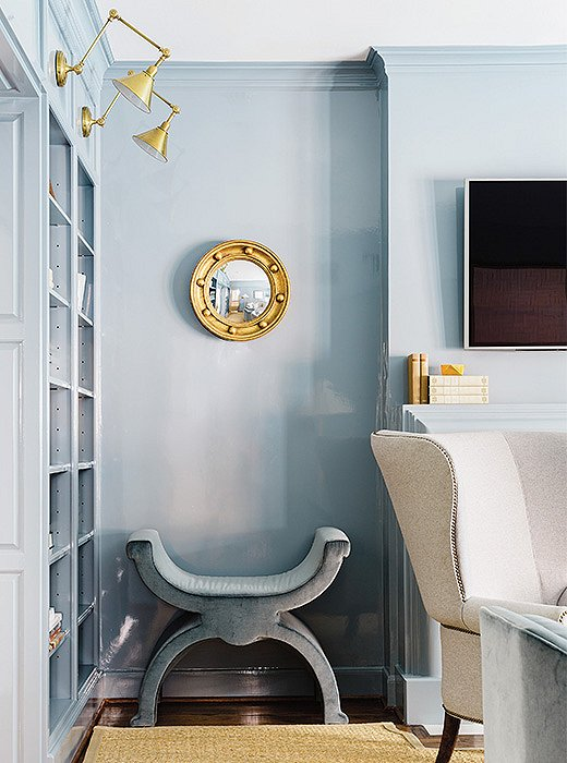 A gold mirror and brass lighting complement a cooler shade of blue.