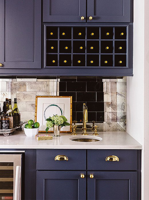 A mirrored-tile backsplash lends glamour to this wet bar.