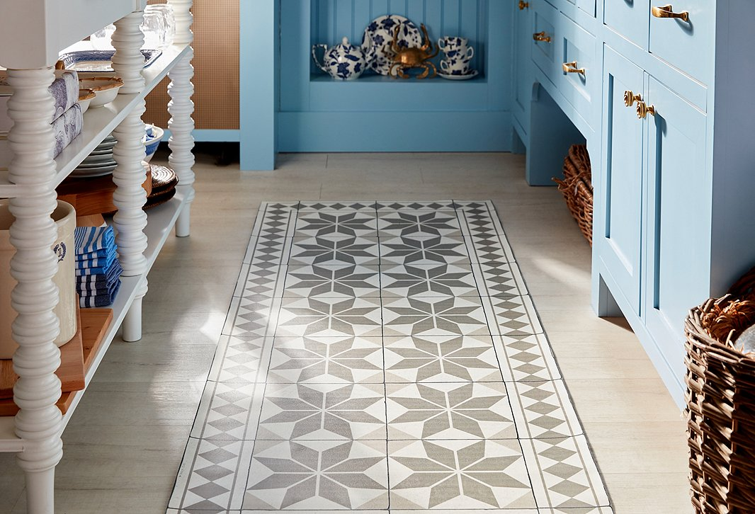 The kitchen features a Mediterranean-inspired, easy-to-clean vinyl floor mat by Beija Flor, along with tableware from Ralph Lauren x Burleigh.