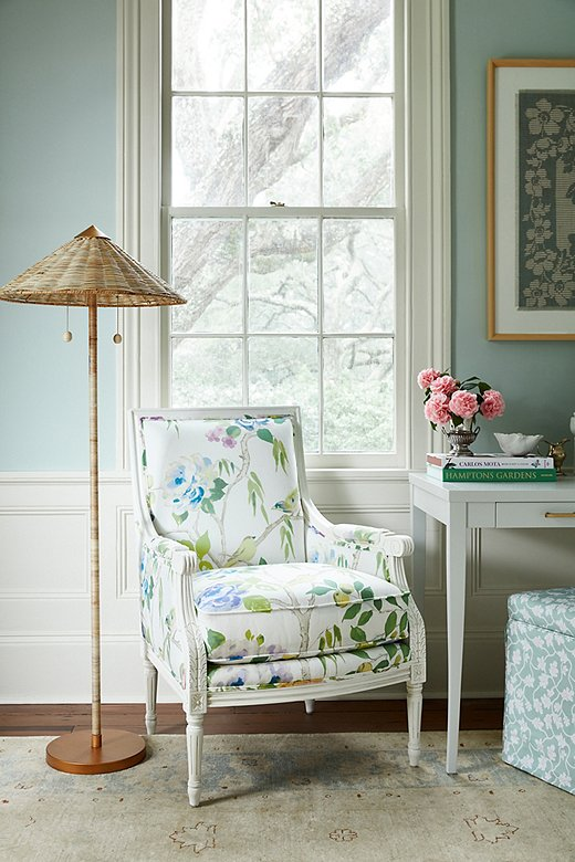 The printof the James accent chair's upholstery is both larger in scale and more airy than floral prints of a generation ago. The Terrace floor lamp, with its rattan shade,counterbalances the chair's refined frame with a touch oftropical texture.