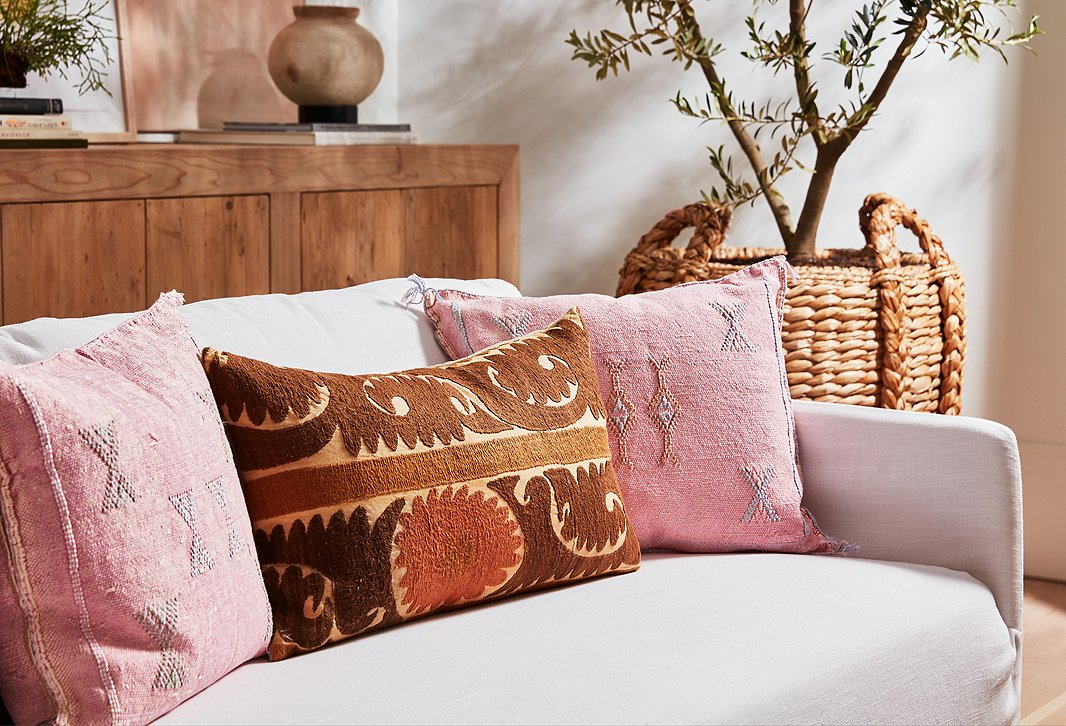 These vintage pillows in pink, brown, and rust brighten up the linen sofa but aren't so vibrant that they detract from the texture of the woven basket that serves as a planter or the robust figuring of the wood buffet.