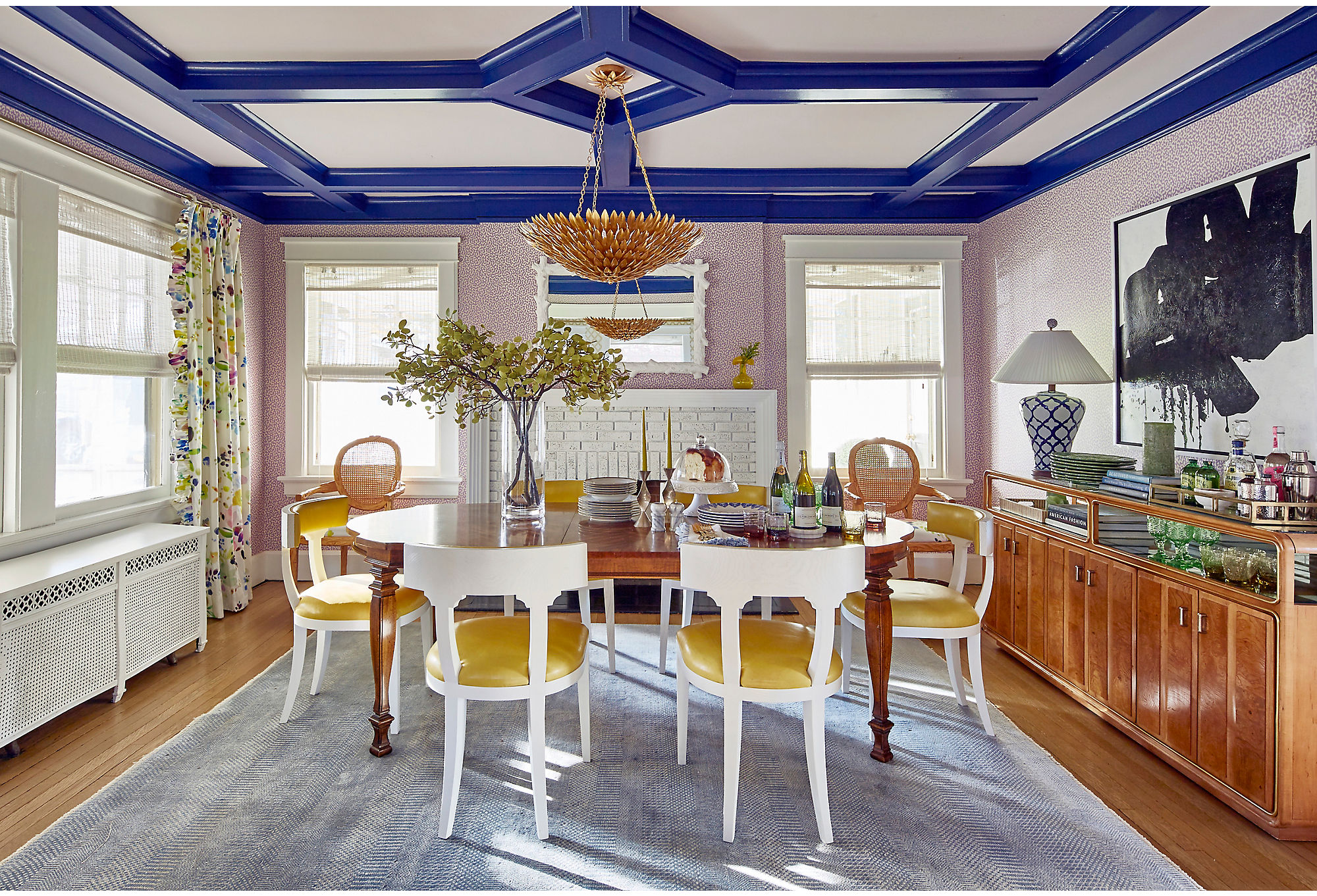 The dining room stuns in an array of color. The ceiling's trim is Blue by Benjamin Moore, while the rest of the room is draped in complementary lavenders and yellows. The yellow seats are an exact match for the yellow lacquer on the foyer's ceiling. Find an identical light fixture here.