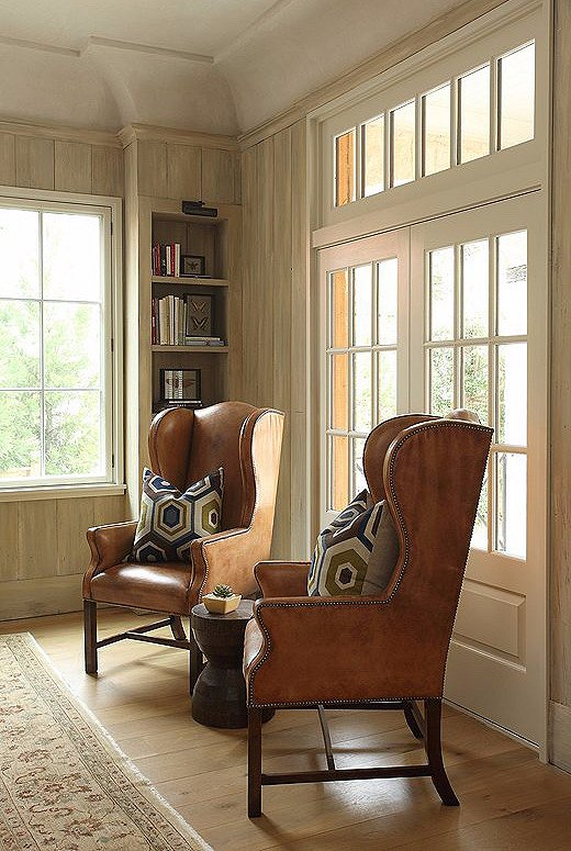Wingback chairs in a saddle leather with funky pillows add a touch of texture to the home. In aspace without a lot of colors, texture is key to adding depth and variety.