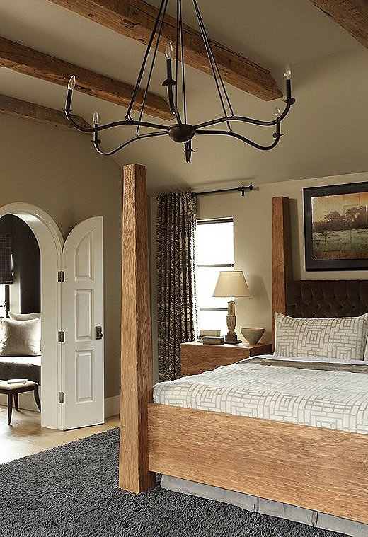 """The couple wanted their master bedroom to feel like a cocoon, says Tish. The custom oak bed anchors the space in a stately manner while providing an interesting symmetry with the wood beams. The headboard is wrapped in a velvet fabric from Ralph Lauren, which Tish says feels like """"a really yummy jacket."""""""