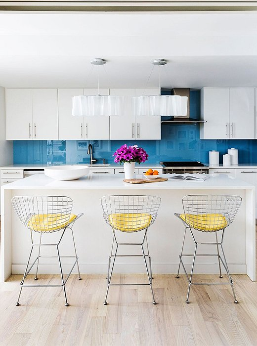 Touches of yellow and blue guide the eye toward the kitchen in the open-plan space.