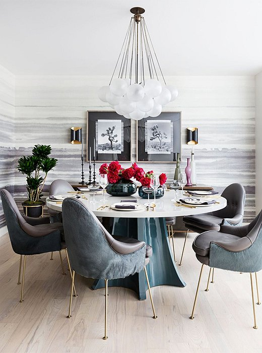 Statement lighting and scenes of Joshua Tree lend life to the dining area. A nonporous table and leather chairs can be easily wiped down in the event of a spill.