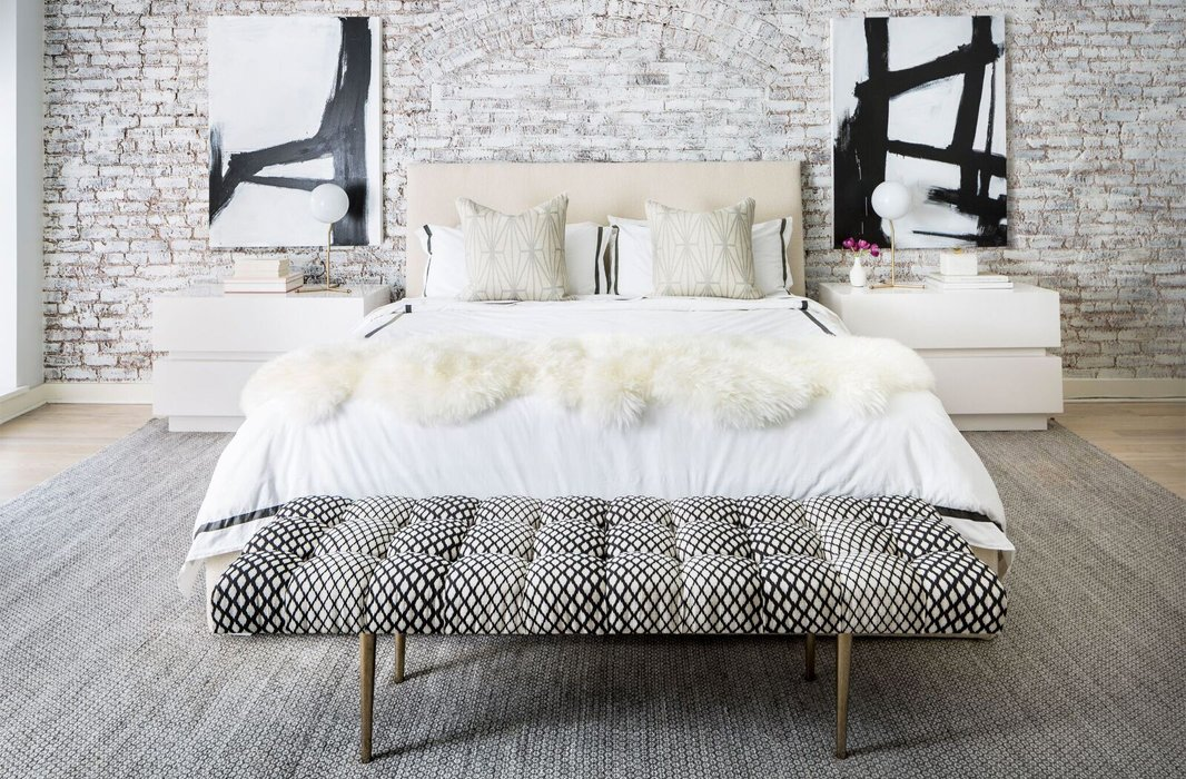 Near-perfect symmetry adds depth and grandeur to the master bedroom. Black-and-white abstracts guide the eye up, while oversize nightstands make the most of the room's length.
