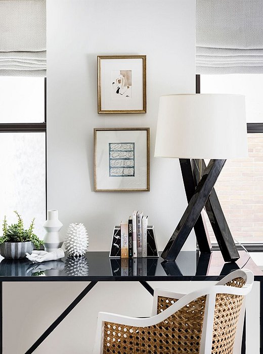 Situated between two windows, a black-lacquered desk echoes the finishes found elsewhere in the apartment. A woven rattan chair adds warmth to the otherwise-cool vignette.
