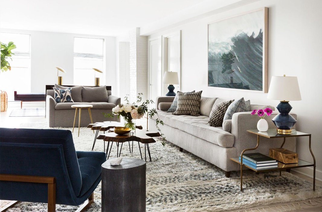 A gray love seat complements a sofa upholstered in a similar hue and a blue midcentury-style chair.