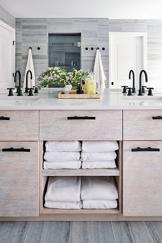 The bathroom's cool palette and streamlined hardwarelean modern. The ingenious touch of farmhouse comes with the rounded-cross sink knobs.