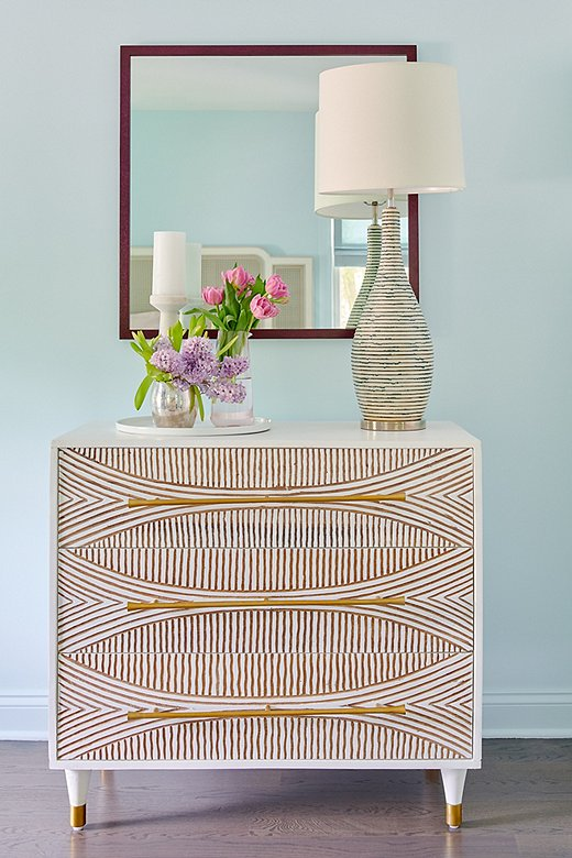 Opposite the caned bed, acarved dresser with gold detail amps up the glam.