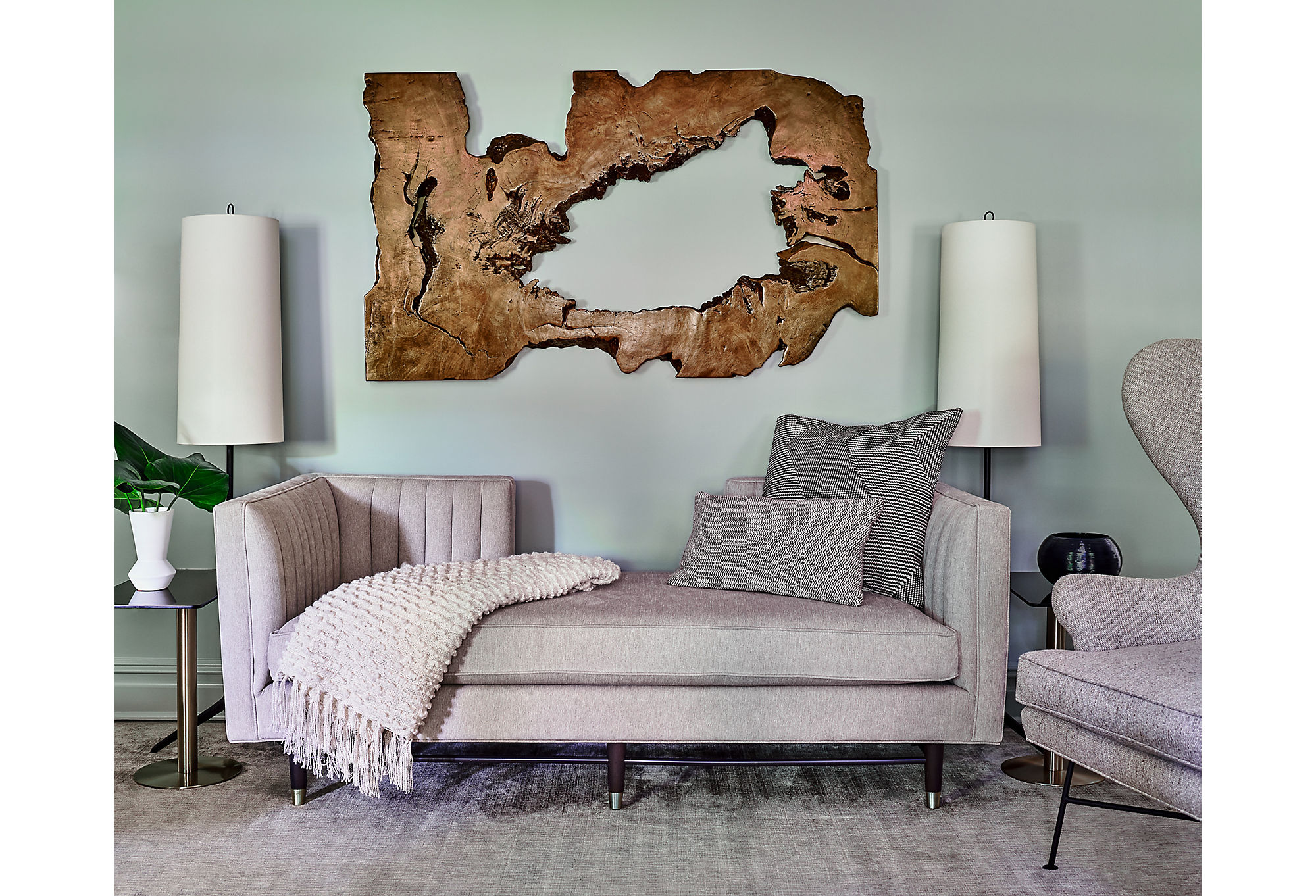 The formal living area uses organic wood art to balance the modern aesthetic of thegray channel-back sofa.