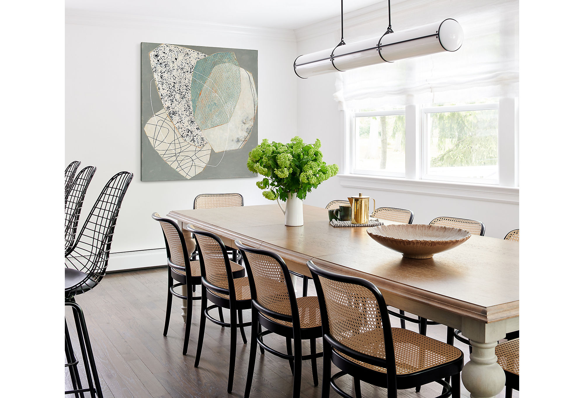 The homeowners have a large immediate family and love to entertain. Tina found a chic farmhouse-style dining table that would seat the entire family for a casual meal. Theart at the head of the table brings in the modern aesthetic.