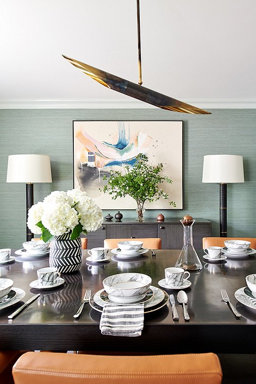 """""""We wanted to incorporate some formality in the dining room,"""" says Tina. She paired a custom table with a textured mahogany sideboard."""