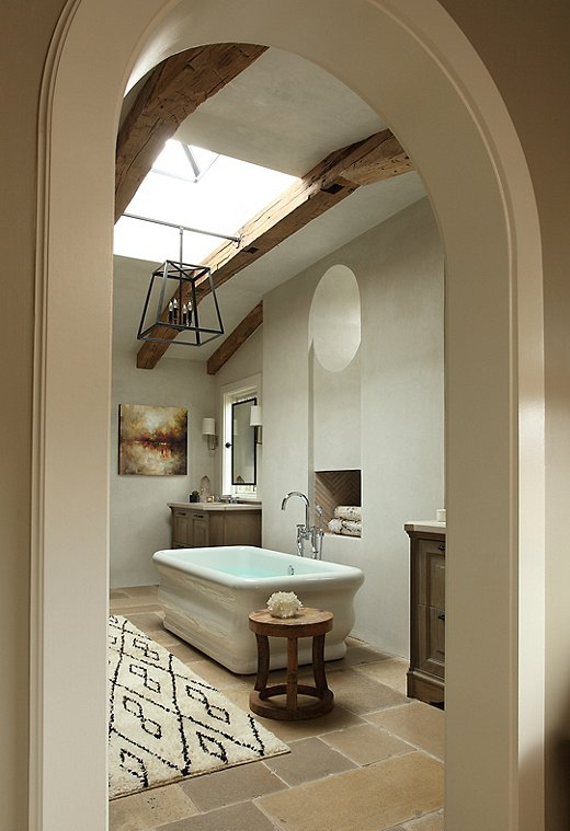 The master bathroom is one of the most compelling spaces in the home. The reclaimed-stone floors from Walker Zanger served as the jumping-off point,dictating the palette, finishes, and decorative accents. Find similar Berber rugs here.
