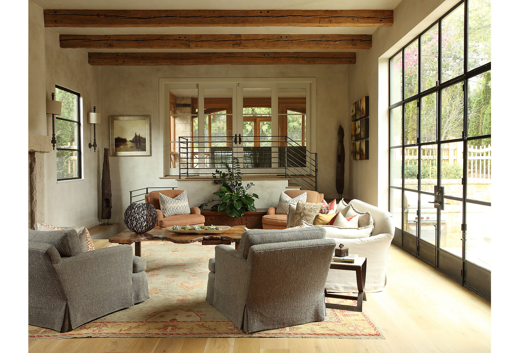 The living room exemplifies the couple's kick-up-your-feet style. Plush sofas and chairs in neutral tones add softness to a space defined by its striking architectural elements.