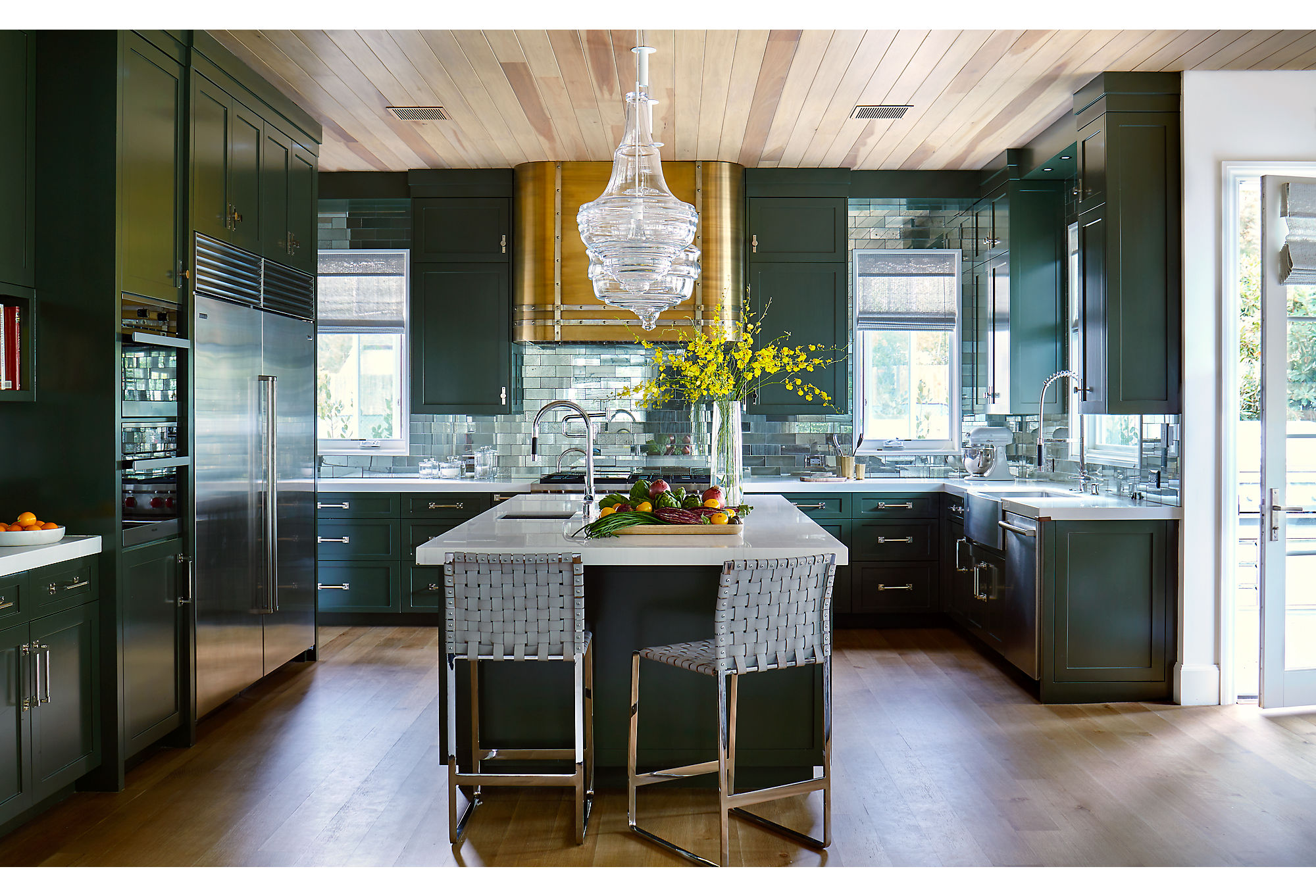 """Glass subway tiles in the kitchen reflect the clients' love of New York City. The hood was a special addition by Adam. """"I wanted it to look like an old metal truck,"""" he says."""