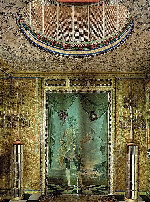 Columns fashioned from air filters flank a door painted by Elizabeth in the entrance hall.