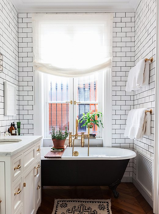 In the home of author and cooking-school founder Alison Cayne, a black-painted claw-foot tub brings a moment of drama to an otherwise all-white space. Photo by Lesley Unruh.