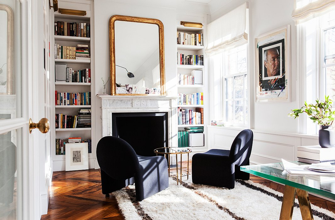 A pair of mod slipper chairs and a Moroccan rug give softness to the light-filled office. The Chuck Close portrait of Jasper Johns at right might be the most colorful piece in the house.