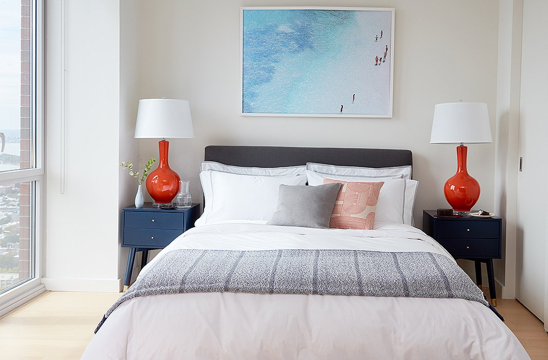 Blue nightstands were selected in the interest of color and storage, pairing perfectly with orange lamps and the oversize aerial photograph hanging above the bed upholstered in charcoal linen.