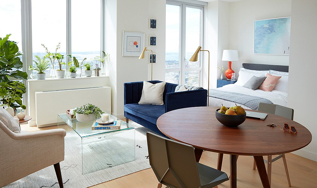 The deep-blue settee adds richness to this studio apartment without making it feel crowded; it also creates a focal point. Room by One Kings Lane Interior Design; photo by Tony Vu.