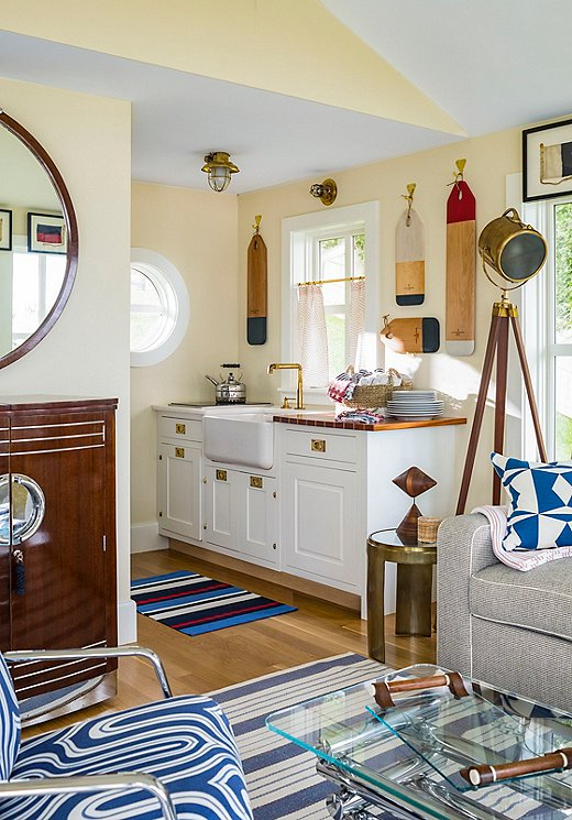 The guesthouse's petite kitchenis home to an apron-front sink, cutting boards painted in a nautical palette hung on the wall, a gauzy window covering from Schumacher, and brass fixtures.