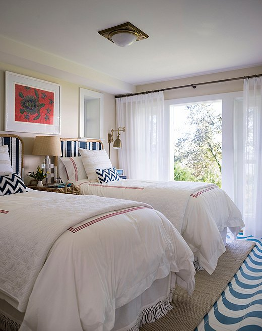 With its cozy twin beds, this bedroom in the guesthouse is perfect for kids. A durable sisal rug sits on top of cement tile flooring, a flush mount from Ralph Lauren Home provides overhead lighting, and turtle art from the clients' travels hangs above the bed.