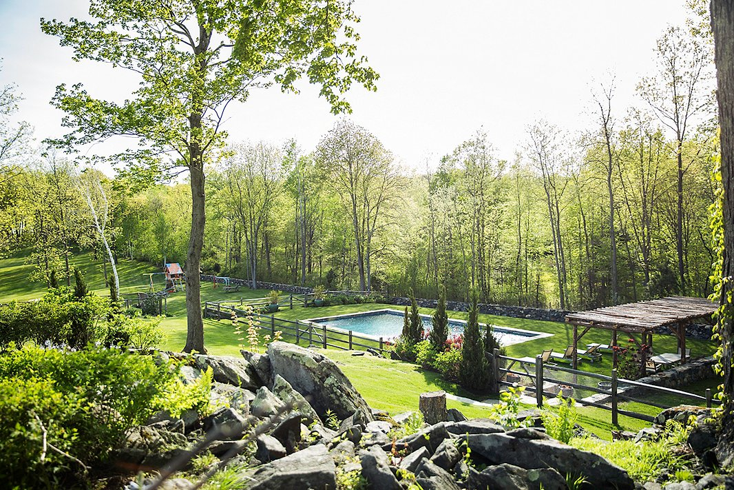 Set farther back from the house, this pool features a rustic wood gazebo and a coordinating fence, taking full advantage of the property's vast acreage. Photo by Lesley Unruh.