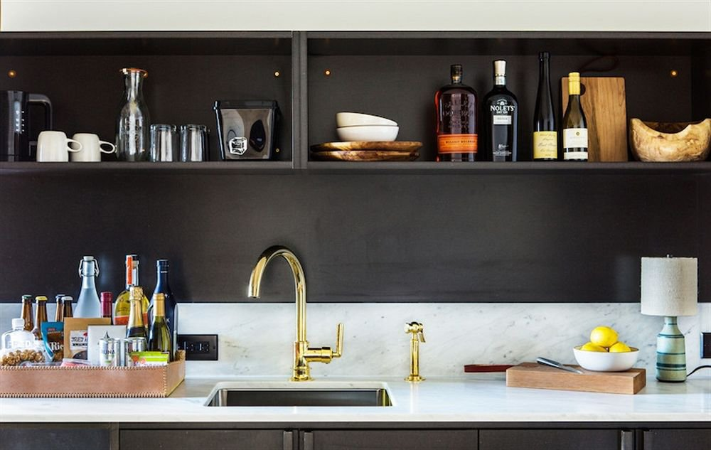 Suites at the Ace get kitchenettes with smart-for-small-spaces open shelving; black-painted, Carrara-marble-topped cabinets (find some of our favorite black wall paint here); and all the fixings for an in-room cocktail party.