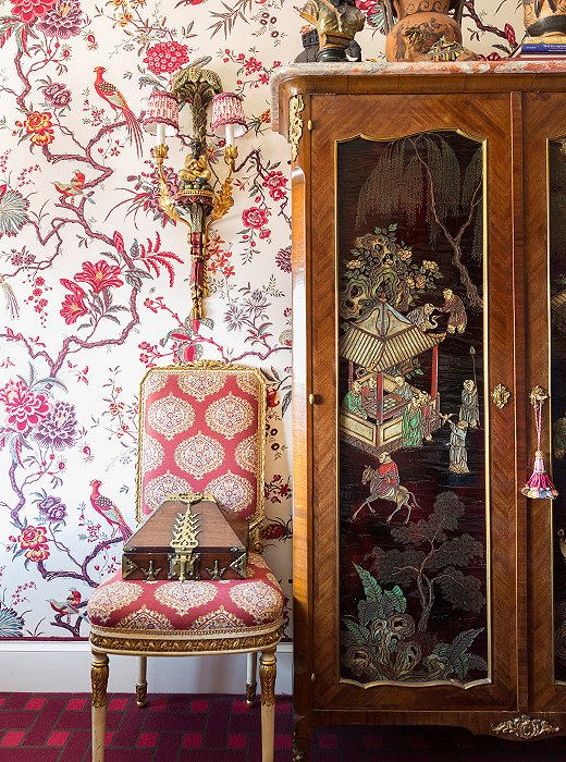 The Chinese armoire, found in London, features lacquered panels that add rich contrast to the upholstered walls.