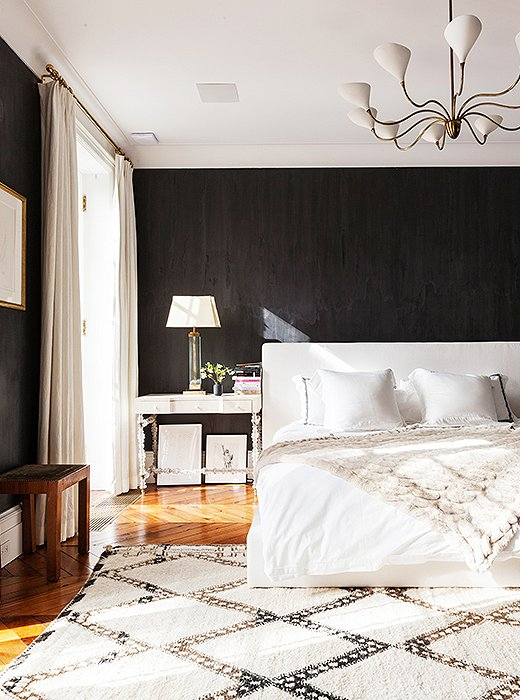 Among the dark walls, the airy white bed seems to float in the center of the bedroom.