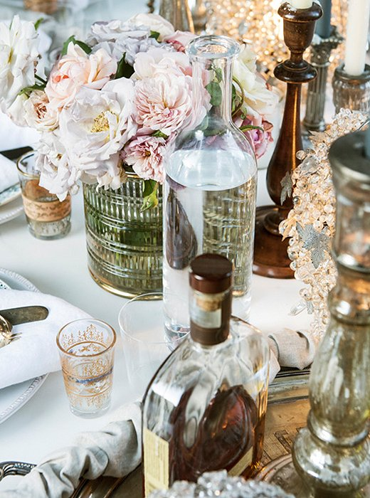 Roses from the garden are placed inlow gold-embellishedglass vessels so that guests can chat without obstruction. Amyalso loves using magnolia leaves or olive branches to dress a table during the cold-weather months.