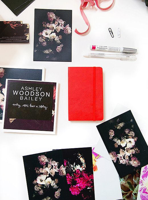 An easy-to-spot red notebook for jotting down inspiration, along with Bailey's work printed on notecards.