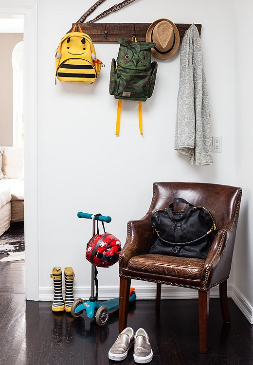 A reclaimed coatrack adds instant functionality to a blank wall by the entry. The leather club chair was a discarded sample that now functions as the perfect place to drop bags or put on shoes.