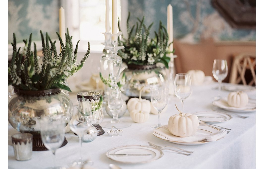 White pumpkins, silvery accents, classic stemware, and gold-rimmed dinnerware make for a decidedly chic and unexpected Thanksgiving look.