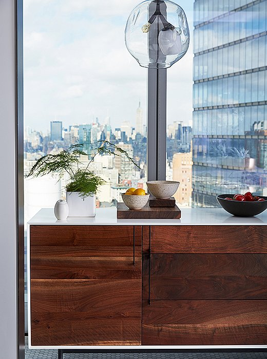 A dramatic view of Manhattan (from 35 floors up) is framed by a walnut-and-lacquer credenza by BDDW and a blown-glass chandelier by Lindsey Adelman. The serveware is from Calvin Klein Home.