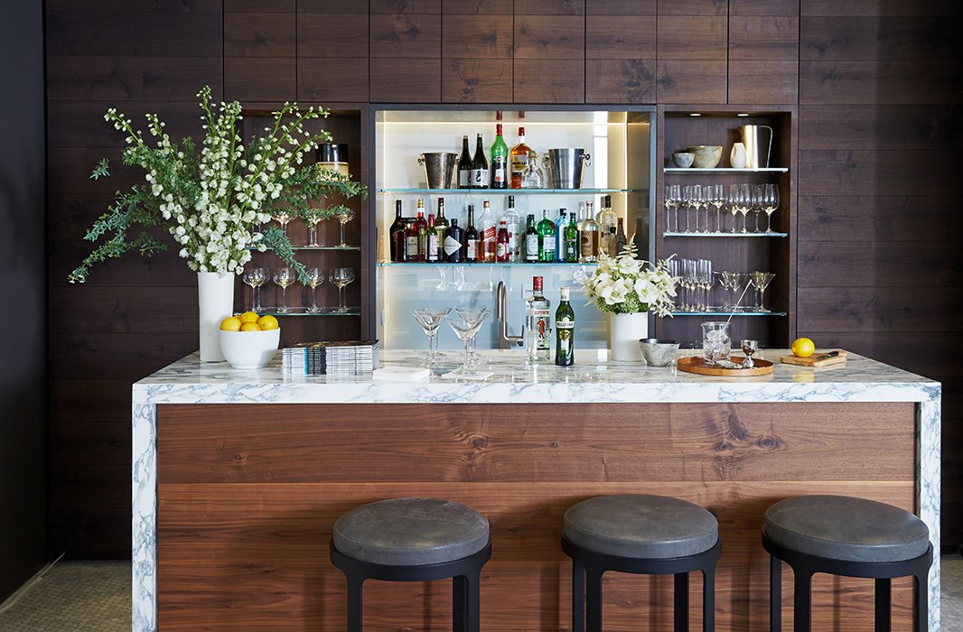 A wide bar leaves plenty of room for cocktail prep. White flowers arranged in white vessels (by Calvin Klein Home) make a dramatic contrast to the dark woodwork.