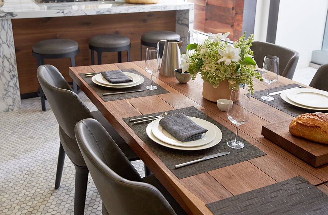 The rugged, organic warmth of the table and table linens balance the cool sleekness of modern dishes and serving pieces. The space is kept perpetually party-ready thanks to a Nest thermostat.
