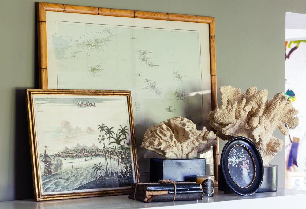 Treasures from the family's travels around the world—framed vintage maps and coral—are grouped atop the white-brick dining room mantel.
