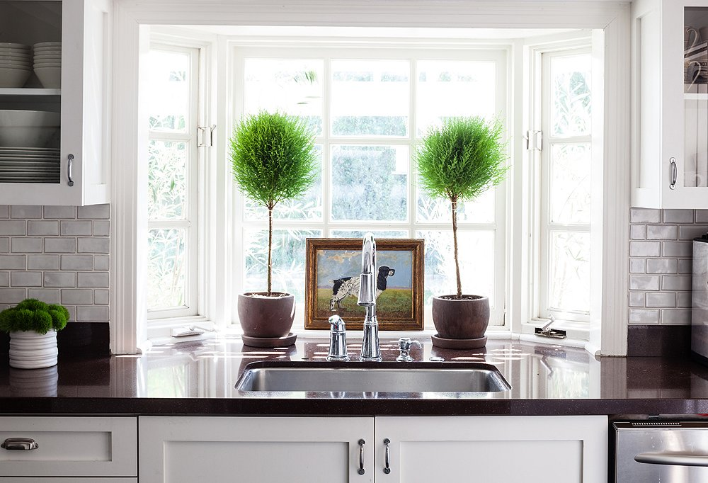 "Bits of color are added to the kitchen through easy-to-change accents such as greenery and a vintage painting. ""I like that it's clean, fresh, white, and bright,"" says Allison."