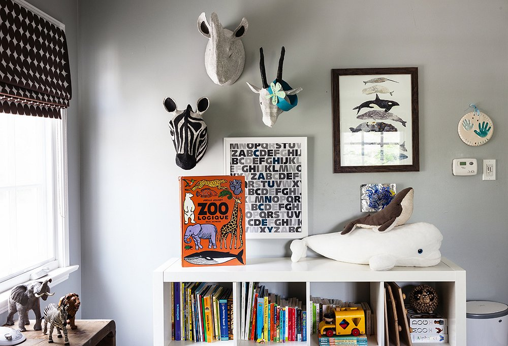 "A salon-style wall is reimagined through a kid's lense with papier-mâché zebra, rhino, and goat heads made with recycled French books. ""Tate loves whales; he's obsessed with them,"" say Mom and Dad of the whale art and stuffed animals."