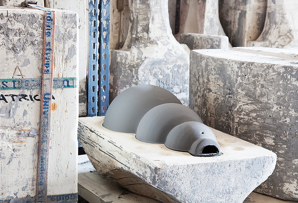 The lamps are first slip-cast by an artisan using a plaster mold and allowed to set for a day before the mold is removed. Here, awinning shape waits patiently to be freed.