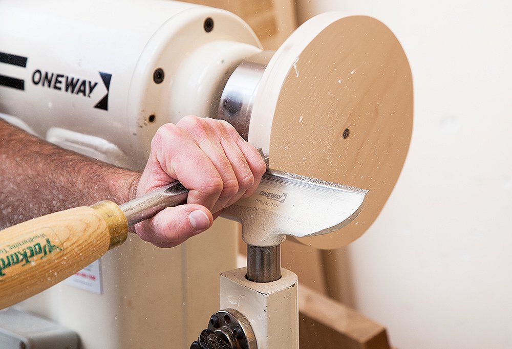 Once the lamps are out of the kiln and approved, a craftsman gets to carving a beautiful wood base.