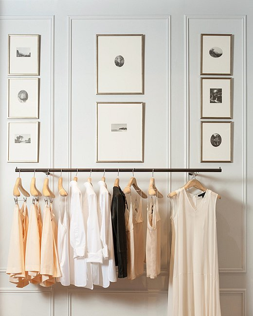 Camisoles and blouses hang below a gallery wall.