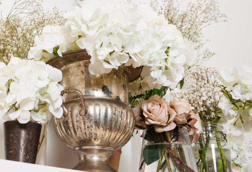 Flowers fill an old silver-plate urn and vintage storage jars, evoking a country home.