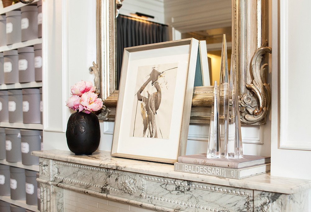 Art, coffee table books, and a gilt mirror add to the illusion of being in someone's home.