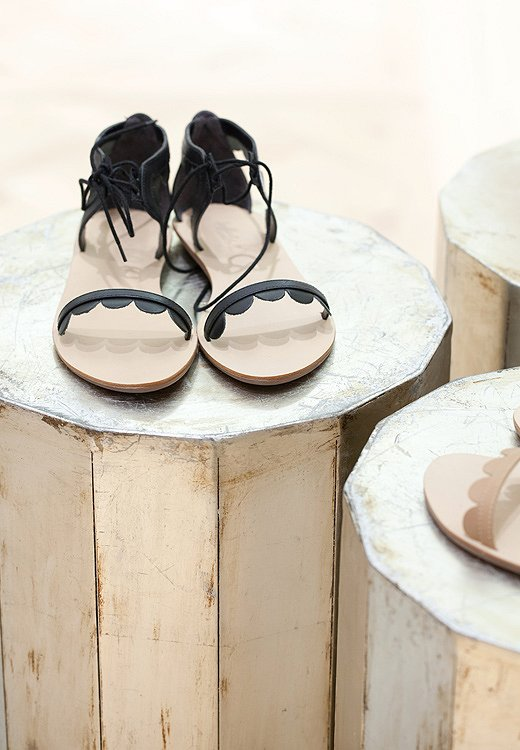 Chipped paint on vintage stools is a striking background for delicate sandals.