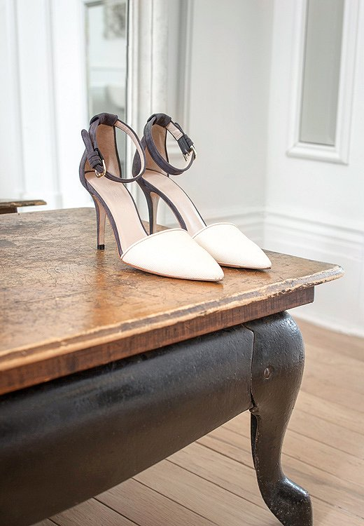 Elegant shoes are placed casually on a vintage table.