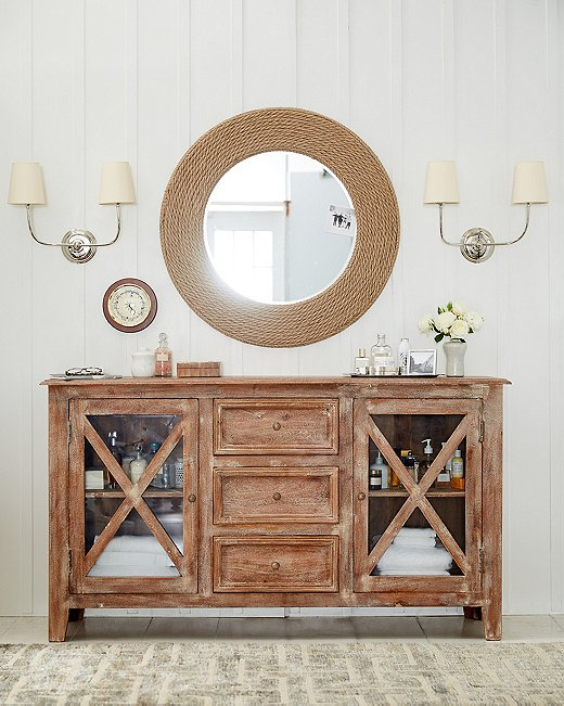 In case the rope frame of the Quincy mirror isn't nautical enough, its shape references a porthole. Adding to the beachy theme is the driftwood-esque finish of the wood buffet.
